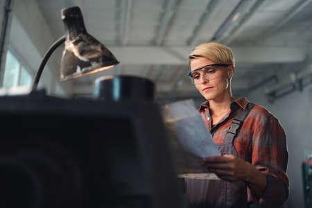 Portrait of young industrial woman working indoors in metal workshop.