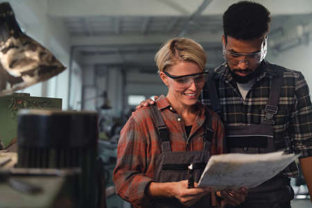 Portrait of young biracial industrial colleagues working indoors in metal workshop, smiling. 스톡 콘텐츠