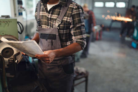 Close up of young industrial man holding blueprints indoors in metal workshop. 스톡 콘텐츠