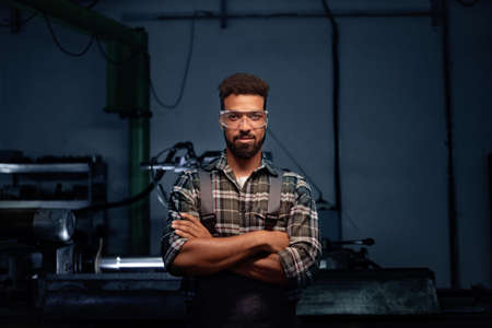 Portrait of young industrial man working indoors in metal workshop, looking at camera.