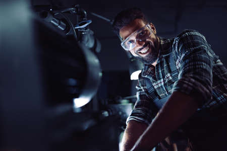 Young african american industrial man during night shift indoors in metal workshop,looking at camera