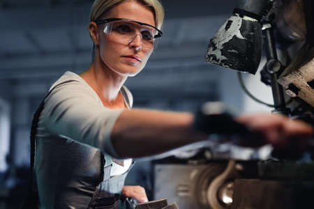 Portrait of mid adult industrial woman working indoors in metal workshop.