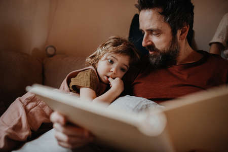 Mature father with small daughter resting indoors at home, looking at photo album. 스톡 콘텐츠