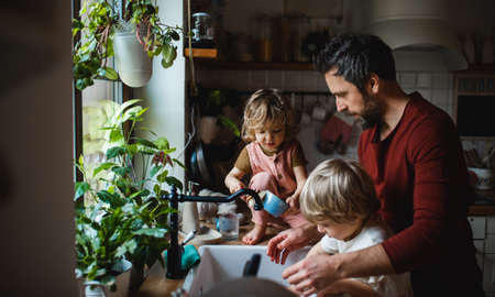 Mature father with two small children washing dishes indoors at home, daily chores concept. 스톡 콘텐츠