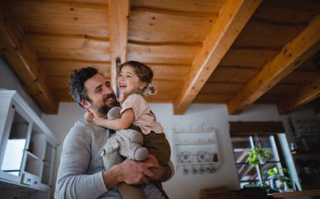 Low angle view of mature father with small daughter having fun indoors at home, holding and hugging.