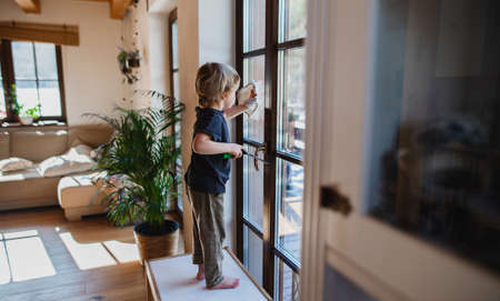 Side view of little boy cleaning windows indoors at home, daily chores concept. 스톡 콘텐츠
