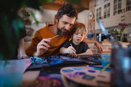 Mature father with two small children resting indoors at home, painting pictures.