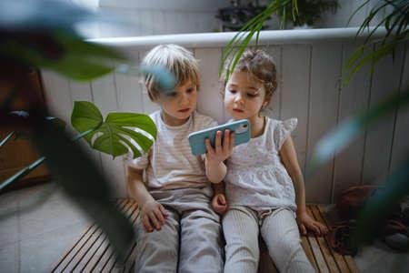 Cute small children sitting on floor indoors at bathroom, using smartphone.