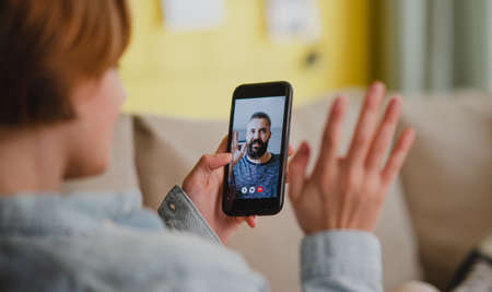 Young woman at home making video call using smartphone, social networks concept.