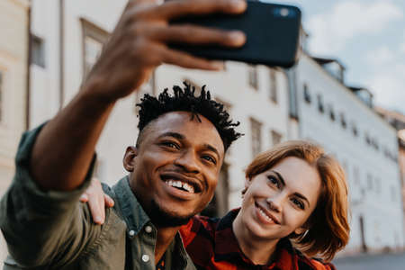 Young biracial couple making selfie for soial networks outdoors in town.