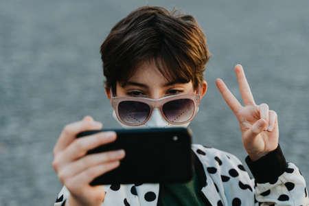 Preteen girl in sunglasses taking selfie for social networks outside in town, coronavirus concept.