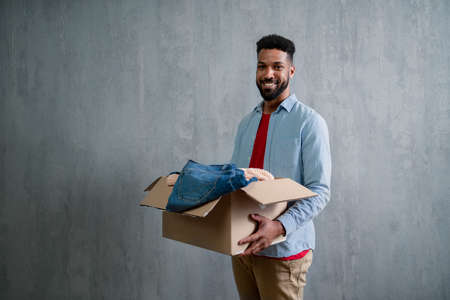 Happy young man holding packing boxes moving home, looking at camera, new living concept.