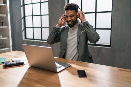 Happy young businessman with smartphone and headset working on laptop indoors in office
