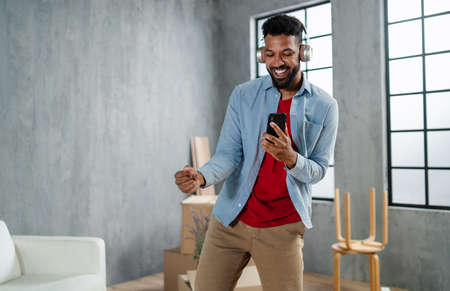 Happy young man with headphones dancing and celebrating moving home surrounded by packing boxes