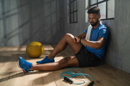 Young African American sportsman sitting and using smartwatch indoors in gym, workout training