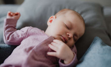 CLose up of cute newborn baby girl, sleeping an lying on sofa indoors at home.