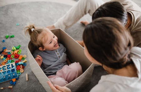 Happy young family with little daughter playing and having fun together at home. 스톡 콘텐츠