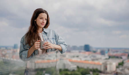 Portrait of young caucasian woman with coffee outdoors on balcony