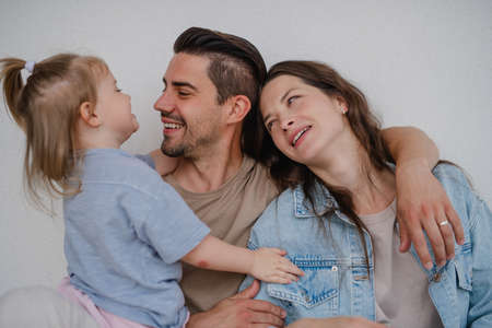 Portrait of happy young parents with little daughter hugging on white background.