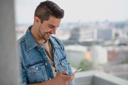 Portrait of young caucasian man with smartphone standing on balcony. 스톡 콘텐츠