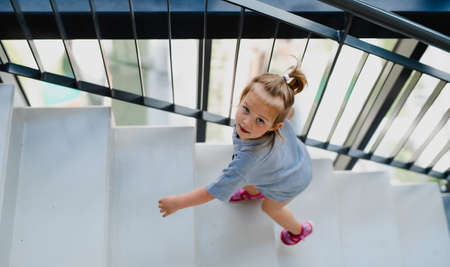 High angle view of little girl walking up the stairs indoors.