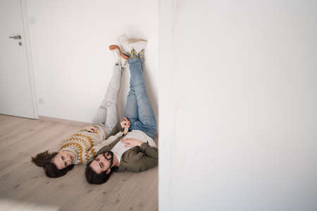 Young couple lying on floor and moving in new flat, looking at camera.