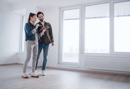 Young couple with tablet moving and planning in new flat, new home and relocation concept.