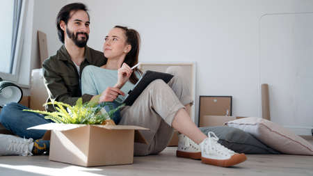 Young couple with tablet sitting on floor and planning when moving in new flat. 스톡 콘텐츠