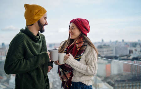 Young couple with coffee standing and looking at each other outdoors on balcony with urban view.
