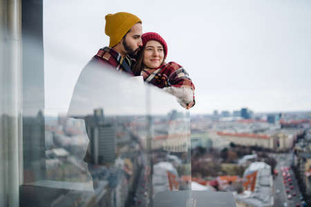 Young couple wrapped in blanket standing and hugging outdoors on balcony, shot through glass. 스톡 콘텐츠
