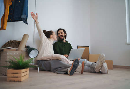 Young couple with laptop sitting on floor and planning when moving in new flat. 스톡 콘텐츠