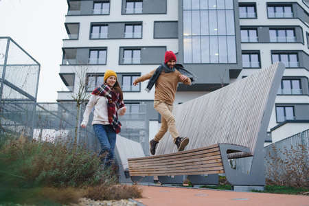 Cheerful young couple owners jumping outdoors in front of new flat, new home and relocation concept.