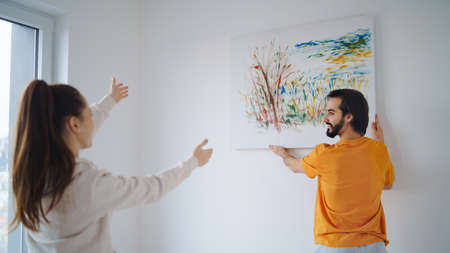 Young couple arranging new flat, hanging up painting, new home and relocation concept.