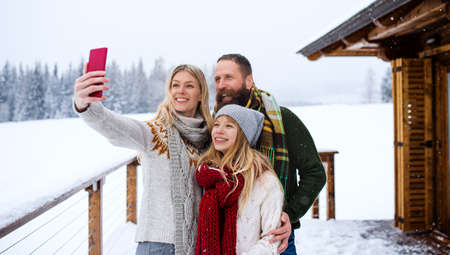 Happy family with small daughter taking selfie by mountain hut outdoors in winter.
