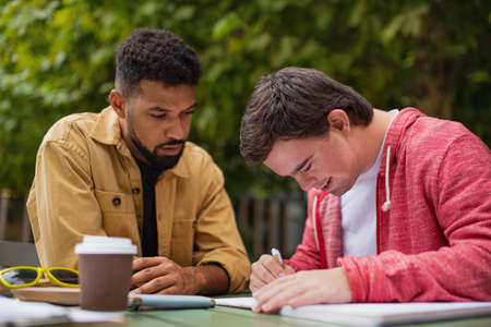 Young man with Down syndrome with his mentoring friend sitting outdoors in cafe and studying.