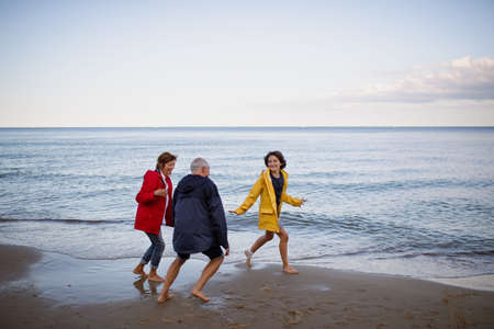 Senior couple and their preteen granddaughter running and having fun on sandy beach.