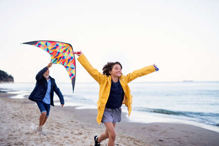 Senior man and his preteen granddaughter playing with kite on sandy beach.