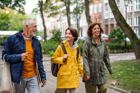 Portrait of happy grandparents with preteen grandddaughter walking together ourtdoors in town street
