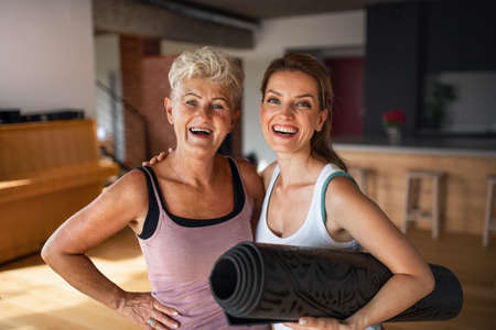 Active senior woman after workout training with adult daughter indoors at home, looking at camera.