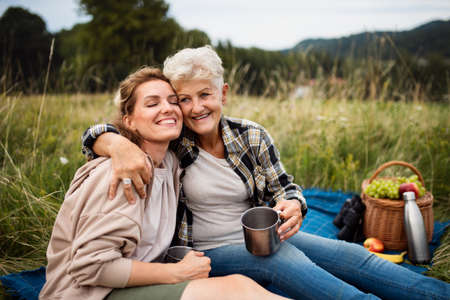 Happy senior mother embracing adult daughter when sitting and having picnic outdoors in nature.
