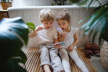Cute small children sitting on floor indoors at bathroom, brushing teeth and using smartphone. 스톡 콘텐츠