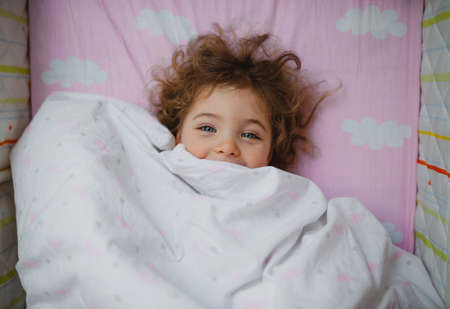 Top view of happy little girl lying in bed hiding under blanket, looking at camera indoors at home