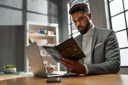 Young african american businessman with diary working on laptop indoors in office 스톡 콘텐츠