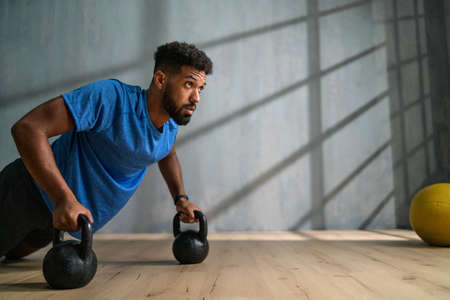 Young African American sportsman doing push ups with kettle bells indoors, workout training concept. 스톡 콘텐츠