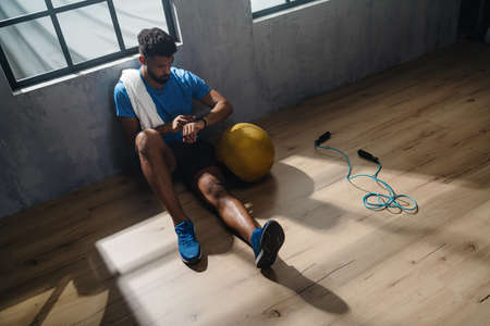 High angle view of young African American sportsman sitting and using smartwatch indoors in gym.