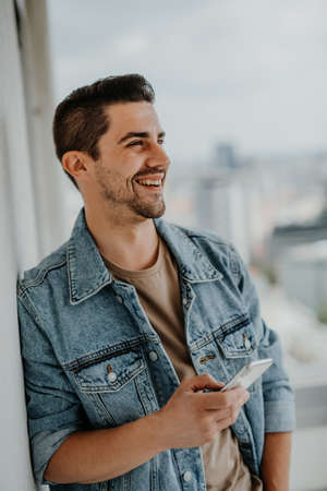 Portrait of happy young caucasian man with smartphone standing on balcony. 스톡 콘텐츠