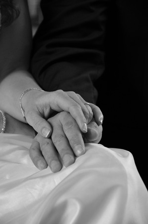 Young couple holding hands at wedding ceremony