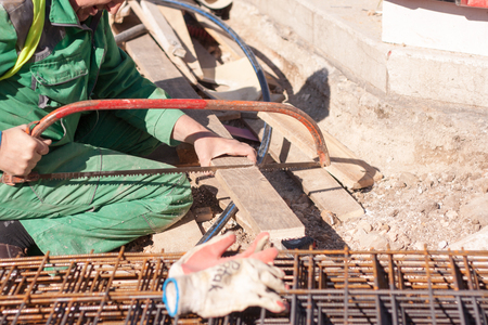 sawing: Worker on a site sawing a piece of wood