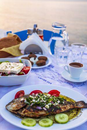 Traditional Cretan Dorada fish with Greek salad, Kissamos, Crete, Greek Islands, Greece, Europe Banco de Imagens