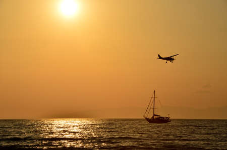 The Airplane and sailboat on sunset background in Rize Akcay Stock Photo